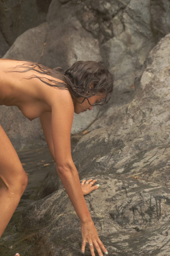 wild woman in nature at rock waterfall in samothraki island in greece nature beauty raw natural elements divinity immortality breathwork rebirther spiritual purification